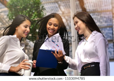 A business women of different ethnicities talk about finance looking at the patterns of economic markets and banks, and in the background a group of multi-ethnic business people. #1103094785