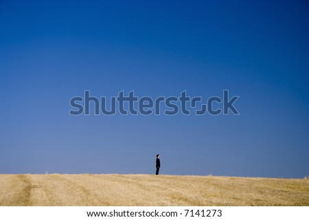 a businessman alone on the top of the field