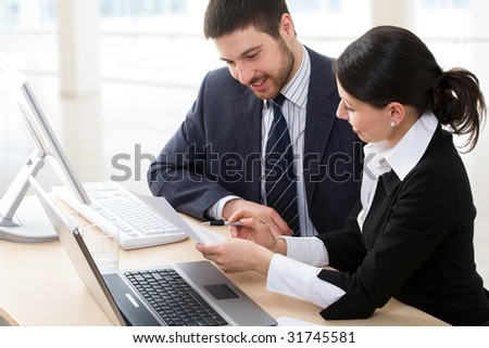 A businessman and a businesswoman working together in the office
