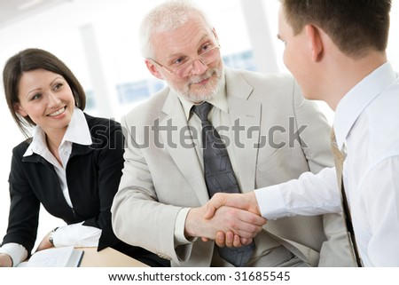 A businessman and two businessman joining, hands in an office.