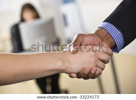 A businessman and woman are shaking hands in an office.  Horizontally framed shot.