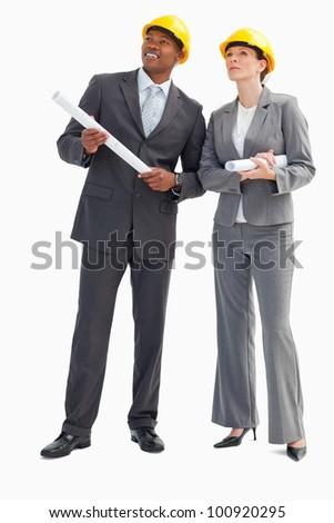 A businessman and woman with notes and hard hats on