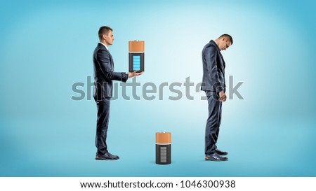 A businessman brings a large fully charged battery to replace a depleted one from inside a very tired businessman. Burning out at work. Charge up yourself. Help from coworkers. #1046300938