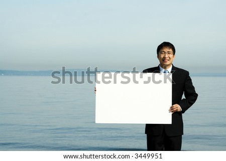 A businessman carrying a blank white board at the beach