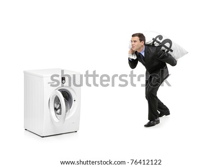 A businessman carrying a money bag and going towards a washing machine isolated on white