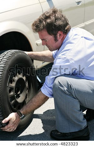 A businessman changing a flat tire on the road, red faced from the heat.