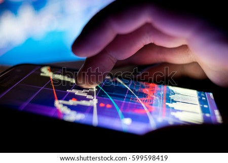A businessman checking stock charts on a mobile device. Technology and work on the go. #599598419