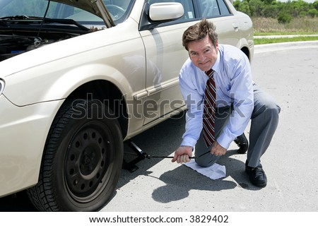 A businessman demonstrating how to use a jack to change a tire.