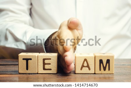 A businessman divides the word Team into two parts. Small grouping. Employee management. Working staff. The organization of the team. The division of work. Efficiency. Separation of powers