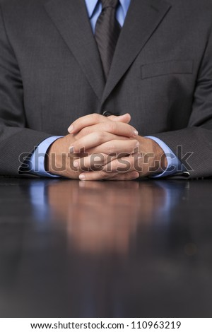 A businessman dressed in a suit sits at a desk with his hands clasped showing power and confidence.
