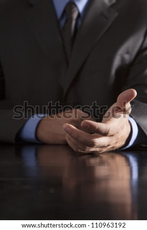 A businessman extends his hand out towards others.