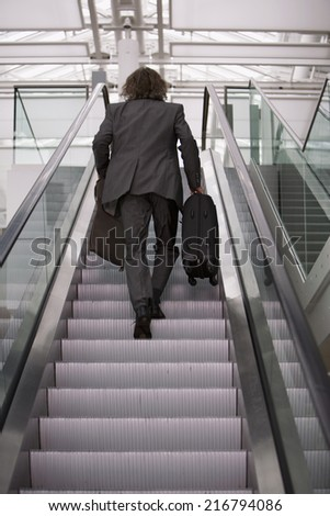 A businessman going up the escalator.