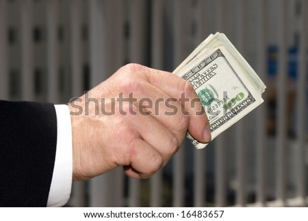 A businessman handing over a wad of cash.