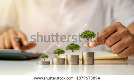 A businessman holding a coin with a tree that grows and a tree that grows on a pile of money. The idea of maximizing the profit from the business investment.