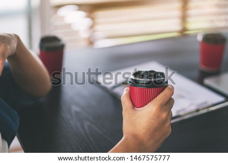 A businessman holding a paper coffee cup to drink while working in a meeting