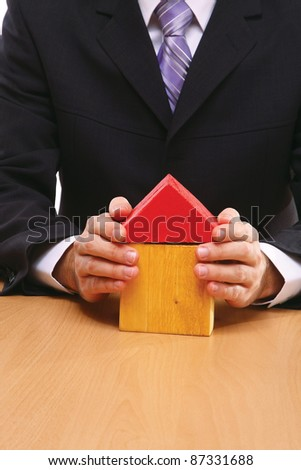 A businessman holding a toy house, real estate presentation, closeup