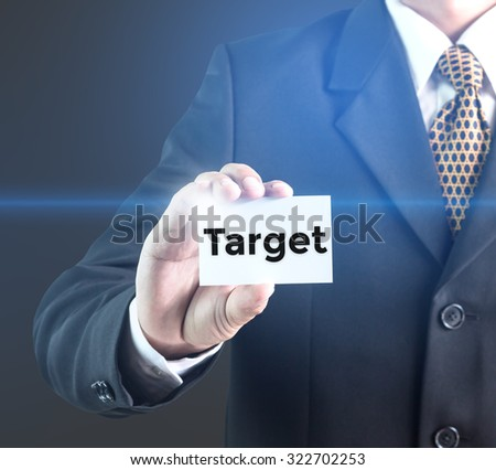 A Businessman holding a white sign with the message target. Can bring to the medium of your ad.
