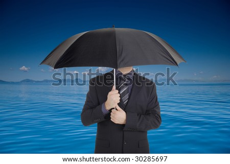A businessman holding an umbrella covering his face