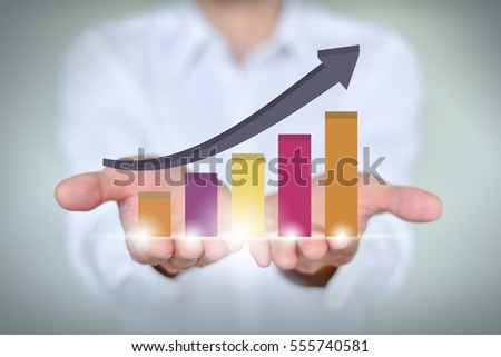 A businessman holding economic growth chart