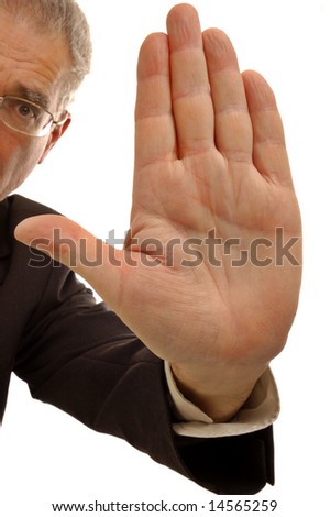 A businessman holding up his hand in a stop sign.
