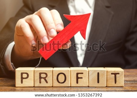 A businessman holds a red arrow up over wooden blocks with the word Profit. Successful business and high profits. Profitability. Revenue growth and capital accumulation. Performance rise #1353267392