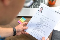 A businessman holds a resume in his hands and conducts an interview with candidates (staff). Attestation, business, education.