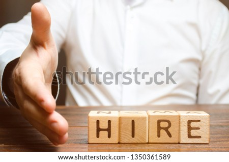 A businessman holds out his hand to shake hands and agree to hire against the background of the word hire. Recruitment concept. Search for employees and professionals on favorable terms.