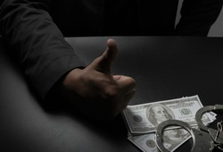A businessman in a black suit, handcuffs on the table against the black table, hands the money to the police for release. Corruption, bribery, illegal transactions.close-up