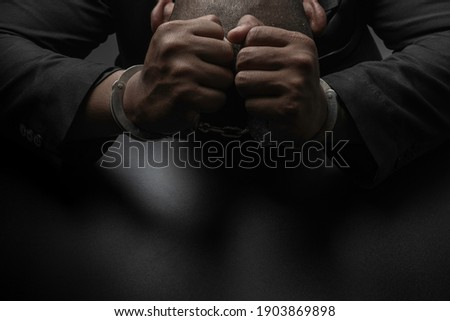 A businessman in a black suit puts handcuffs on the table and the black table. Corruption, bribery, illegal transactions Stock photo ©