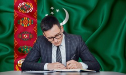 A businessman in a jacket and glasses sits at a table signs a contract against the background of a flag turkmenistan