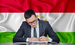 A businessman in a jacket and glasses sits at a table signs a contract against the background of a flag Tajikistan