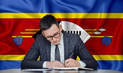 A businessman in a jacket and glasses sits at a table signs a contract against the background of a flag swaziland