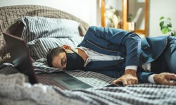 A businessman in a suit and mask is sleeping in bed next to a laptop and phone after a hard day's work. The concept of fatigue and exhaustion from hard work during a pandemic