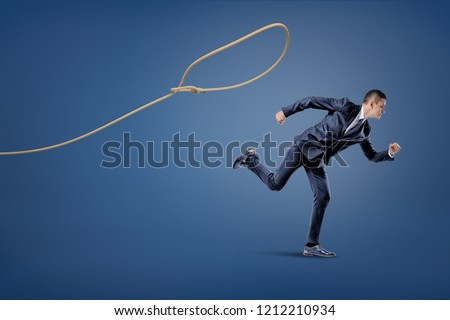 A businessman in a suit runs away from a rope lasso that tries to catch him. Business and chance. Getting away from trouble. Evading prosecution.