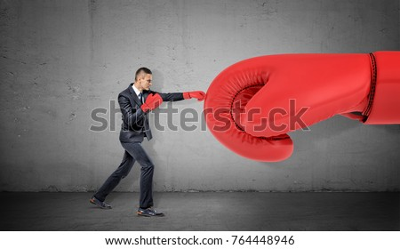 A businessman in boxing gloves on concrete background punches a giant red glove. Business and competition. Training to win. Overcome difficulties.