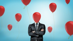 A businessman in front view with crossed arms stands surrounded by many red party balloons with one hiding his face. Businessman in disguise. Entertainment business. Birthday at work.