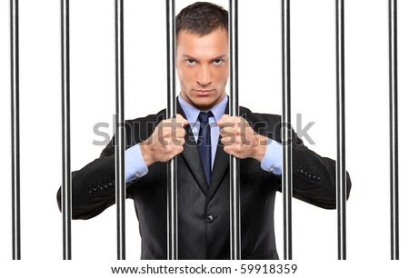 A businessman in jail holding bars isolated on white
