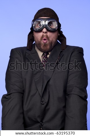 A businessman in old fashioned flight helmet and goggles with a silly expression.