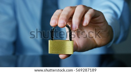 A businessman in shirt and tie shows a padlock as a sign of security.The padlock symbol password that protects the system files from technological hacker internet or banking system.