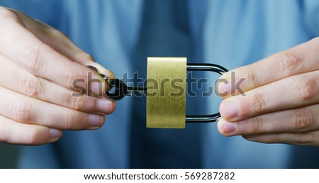 A businessman in shirt and tie shows a padlock with keys as a sign of security.The padlock symbol password that protects the system files from technological hacker internet or banking system.
