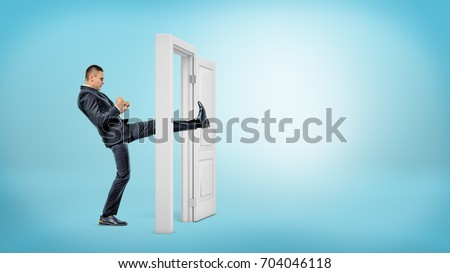 A businessman in side view kicks a small white door open with his leg on blue backgrounds. Business and success. Opening all doors. Aggressive business approach. #704046118