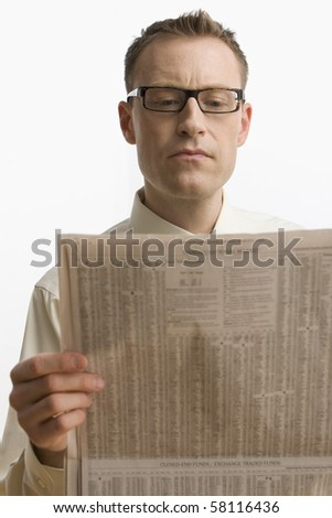 A businessman intently reads the newspaper.  Vertical shot.  Isolated on white.