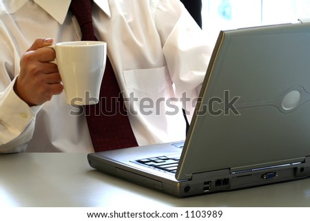 A businessman is drinking a cup of coffee and working on his laptop