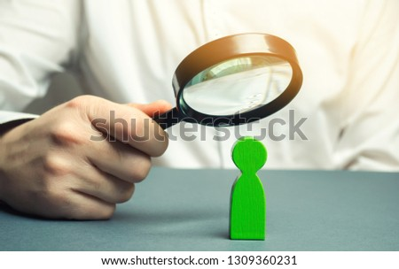 A businessman is holding a magnifying glass over a green man figure. Search for a talented employee. Identifying strengths in the company. Disclosure skills. A candidate for promotion by duty.