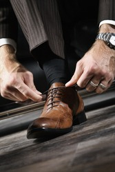A businessman is lacing his shoes