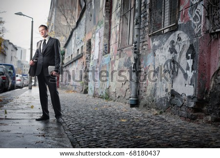 A businessman is looking around in a poor neighborhood