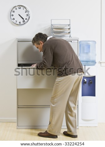 A businessman is looking through a drawer at an office.  Vertically framed shot. - stock photo