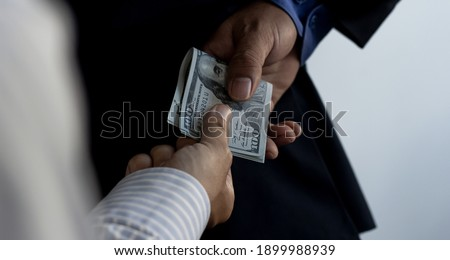 A businessman is sending a dollar to a business partner as a bribe. Bribery is corruption, and the company is punishable by law. The concept of bribery. ストックフォト ©
