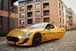 A businessman is sitting in a golden car. A man is driving inside a car. Driver. Chic man with glasses, with a perfect haircut, glasses, fashionable. Freelancer. Rich boy. A teenager drives a car.