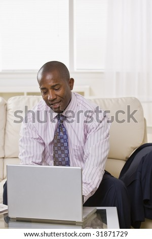 A businessman is sitting on a couch and working on a laptop.  He is looking away from the camera.  Vertically framed shot.